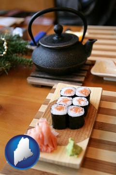 sushi and green tea being served at a Japanese restaurant - with Maine icon